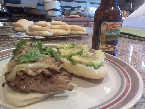 A homemade sandwich of pork shoulder, caramelized onions, avocado and cilantro on a coco bread roll