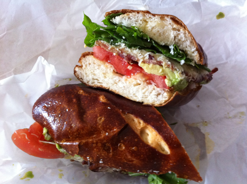 Tomato, arugula, avocado, parmesan, bacon and olive oil on a delicious brown sweet pretzel roll.