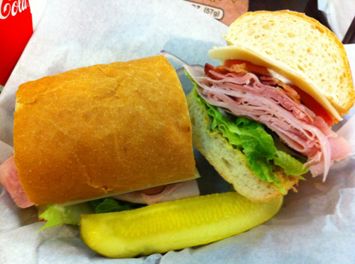 A picture-perfect deli-sliced ham sandwich. Three types of ham piled high, bacon, provolone and accoutrement on a white roll. A pickle spear supports the composition.